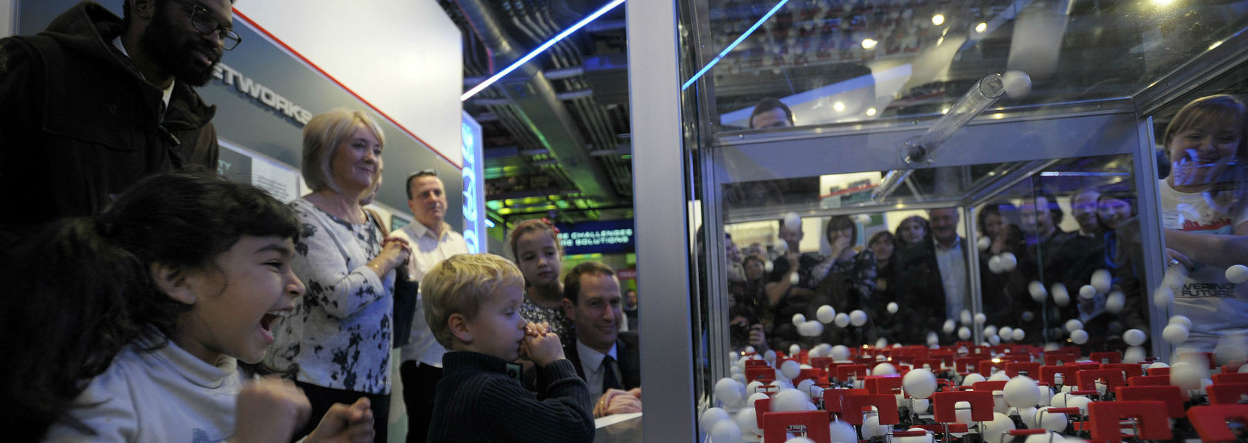 A crowd of mixed ages watch on in excitement at an exhibit demonstrating a chain reaction