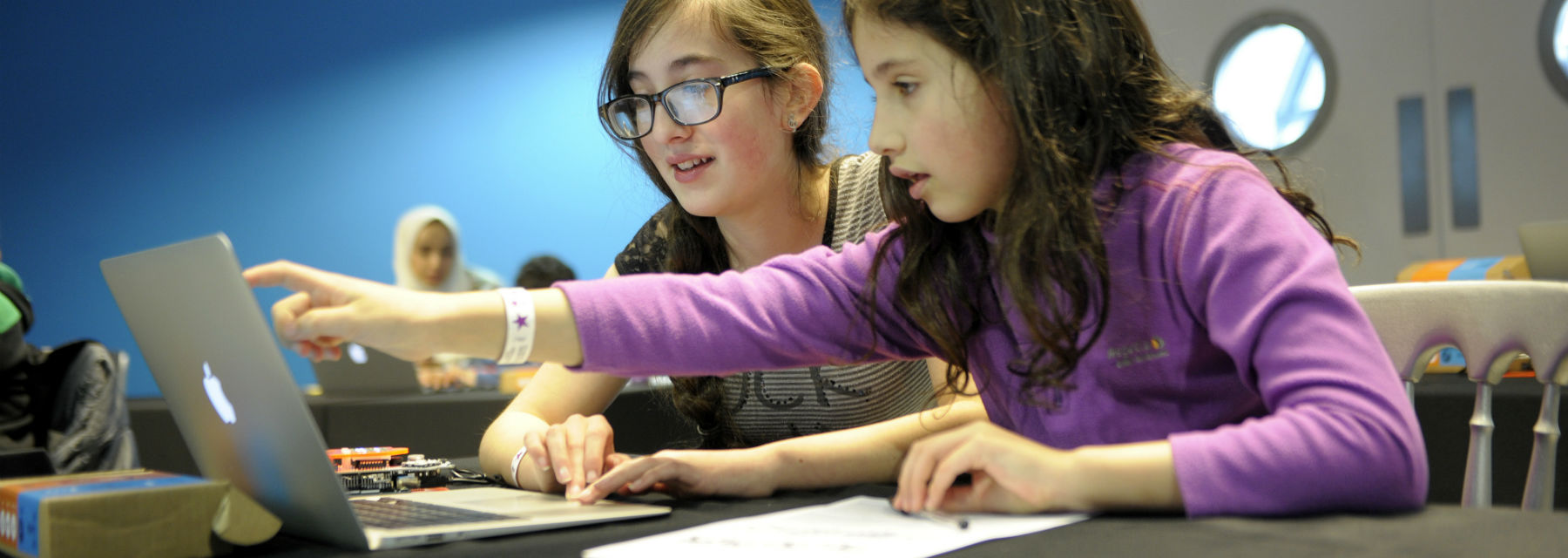 Two girls working at a laptop in a coding workshop