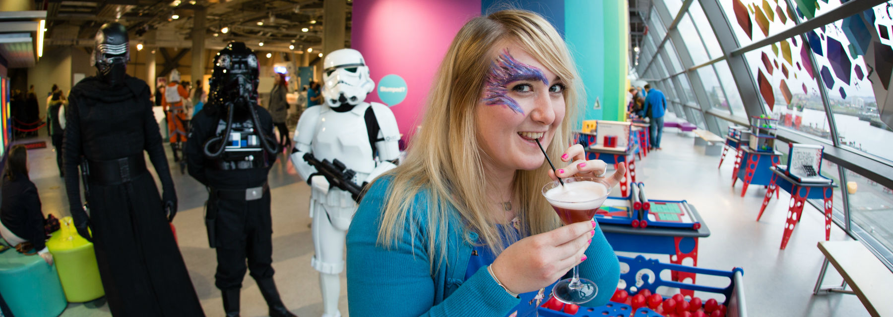 A woman drinking a cocktail amongst the science centre exhibits, with characters from Star Wars behind her