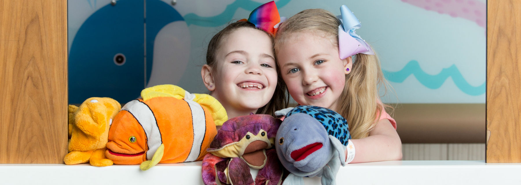 Two smiling girls put on a sea creature puppet show