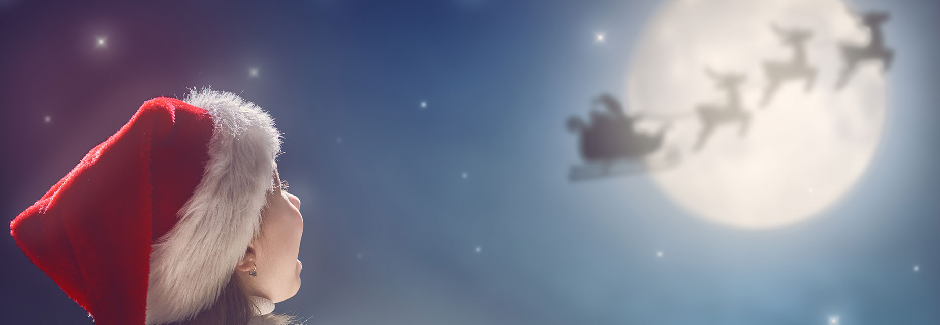 A young girl looks into the sky at a silhouette of Santa's sleigh against the moon