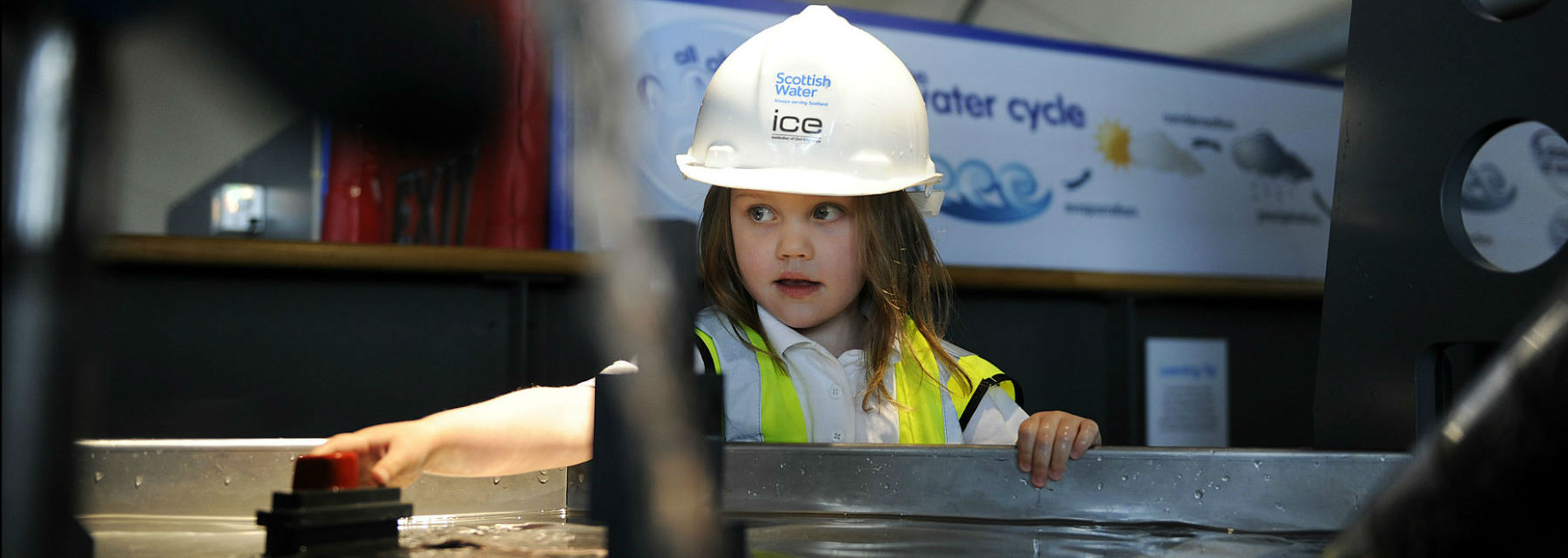 A girl wearing a helmet and high vis vest plays at a water exhibit