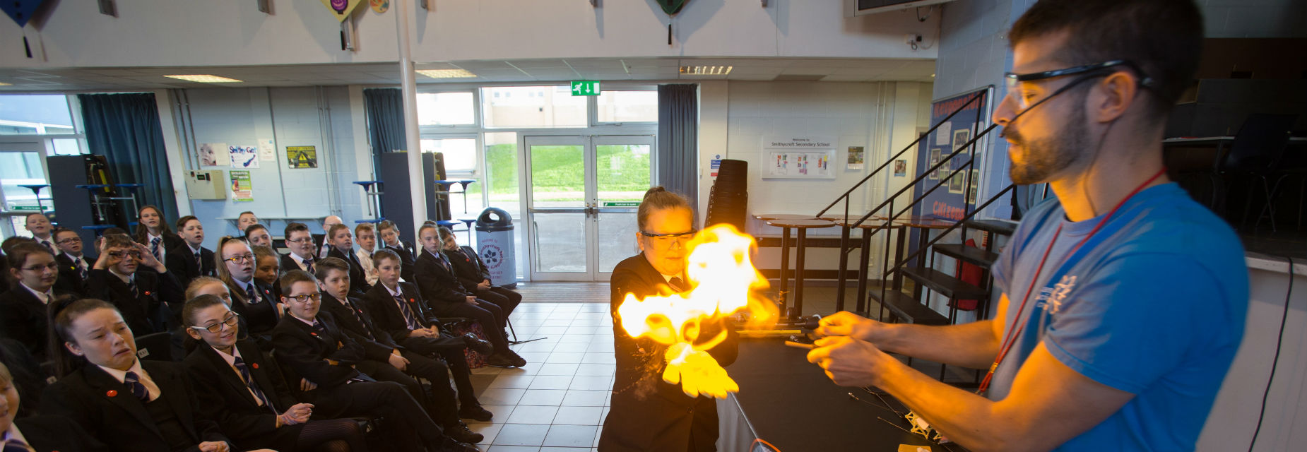 A science communicator and pupil produce a flame in an experiment in front of an audience