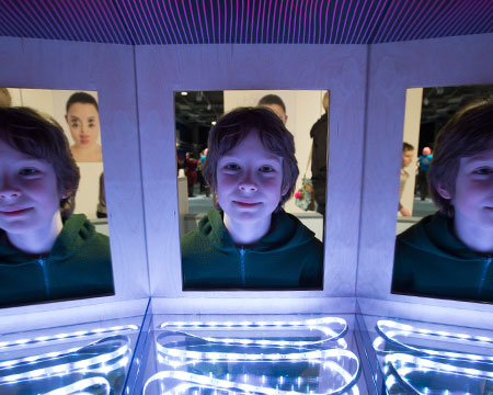 A young visitor interacts with the infinity mirror exhibit in our Question of Perception Exhibition