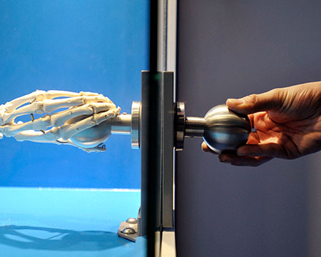 A hand holding onto a doorknob with a skeleton hand attached to the other side