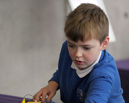 A young pupil interacts with electrical components to construct a car