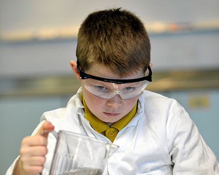 A pupil pours liquid from a jug whilst wearing goggles and a lab coat