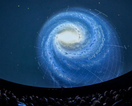 An audience listens to a speaker at a David Elder lecture in the Planetarium. An image of a galaxy is projected onto the dome of the Planetarium.