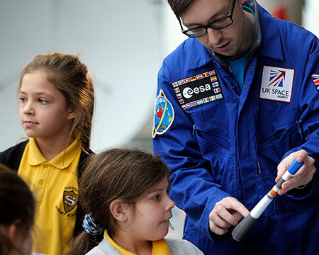 A Science Communicator talks to a young pupil about her model rocket