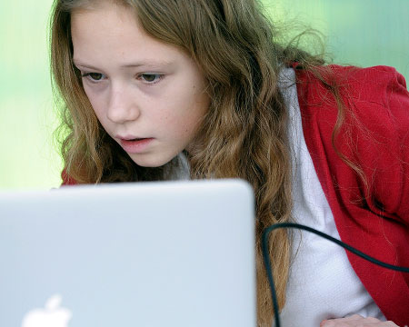 A pupil codes her own games on a laptop in our workshop area
