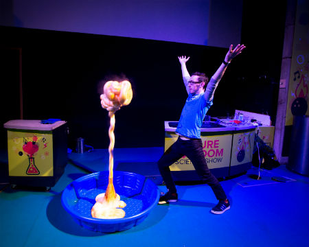 A science communicator on stage performing the Elephant's Tootpaste demo. A plume of 'toothpaste' rises up to almost the same height as the presenter.