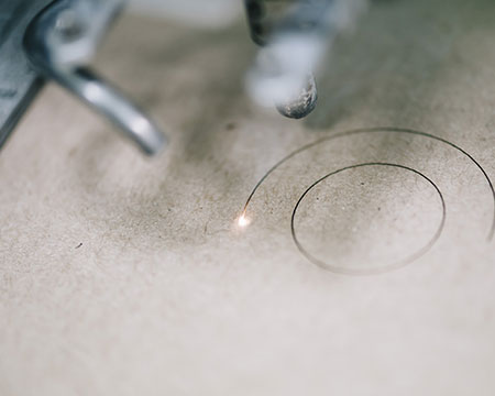 A laser cutter being used to cut circles into particle board