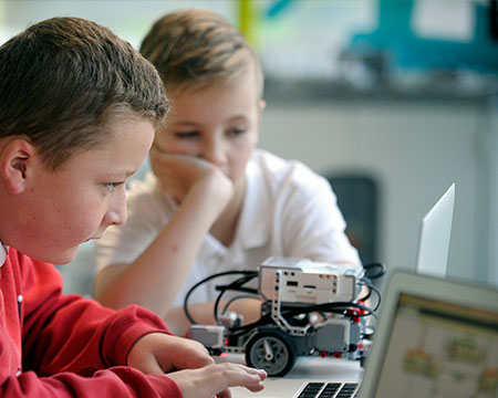 Pupils engaging with Lego® technology, programming on a laptop