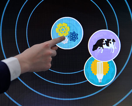A finger pointing to a touch screen exhibit in the My World of Work Live! exhibition