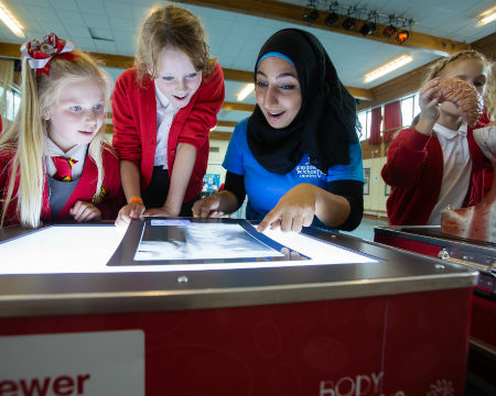 School pupils and a science communicator look at an illuminated X-ray image