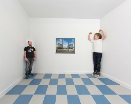 A girl appears much taller than a man in a forced perspective room