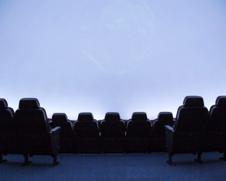 Looking out from behind the seats of the planetarium onto the screen