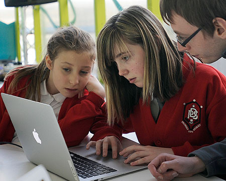 Two girls look use a laptop for coding with the help of a GSC instructor