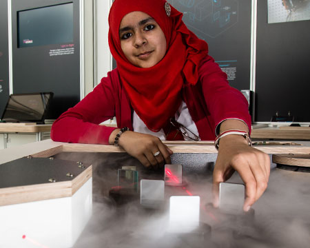 A pupil interacts with the laser fog table exhibit in Quantic