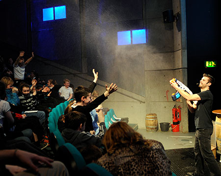 A presenter of our Science Show 'Water Water Everywhere' spraying the audience with a water gun in the Science Show Theatre