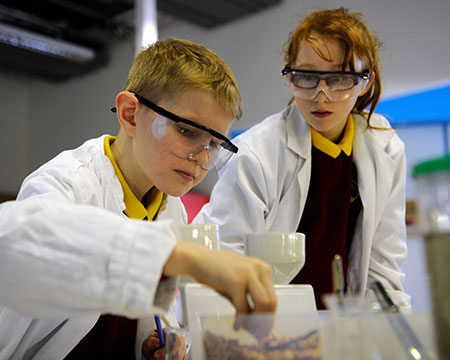 Two young pupils in lab coats and goggles engage in water experiments