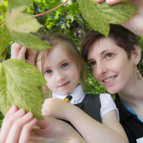 A school pupil and OPAL Community Scientist from GSC examine leaves on a tree