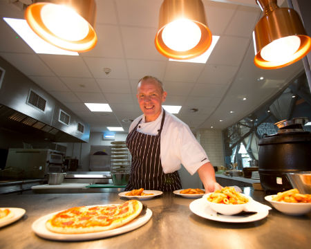 A chef presents plates of food under hot lamps