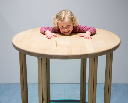 An optical illusion shows a girl's head, shoulders and arms resting on a table.