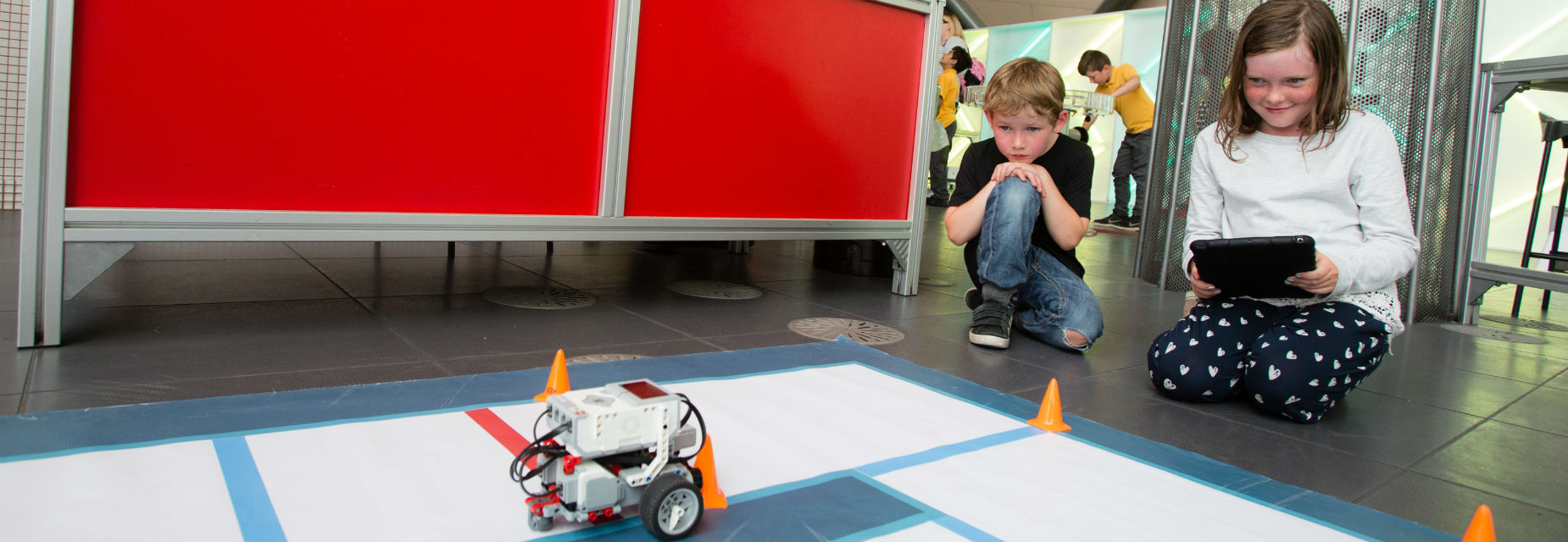 Boy and girl controlling the lego mindstorm robot