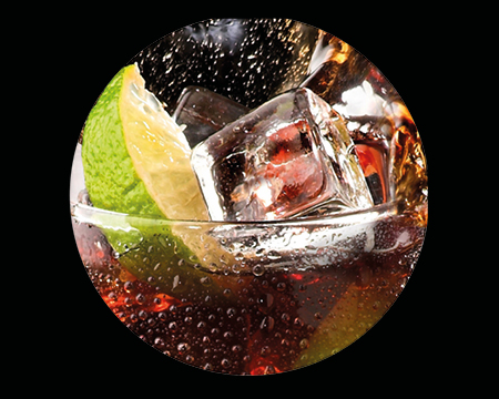 Dark rum in a glass with ice and a lime wedge