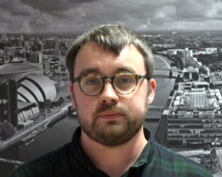 Sam standing in front of a photograph of Glasgow
