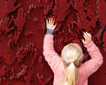 Girl using Pin Screen Wall exhibit