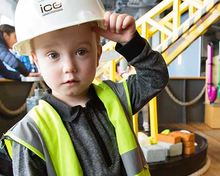 A boy wearing a hard hat and high visibility vest