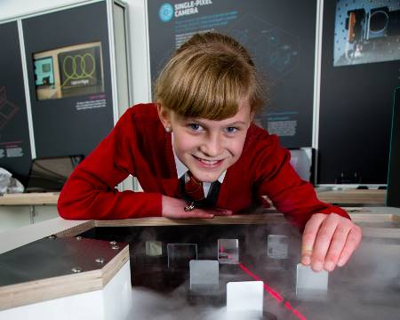 A pupil looks at the passage of laser beam through mirrors and smoke