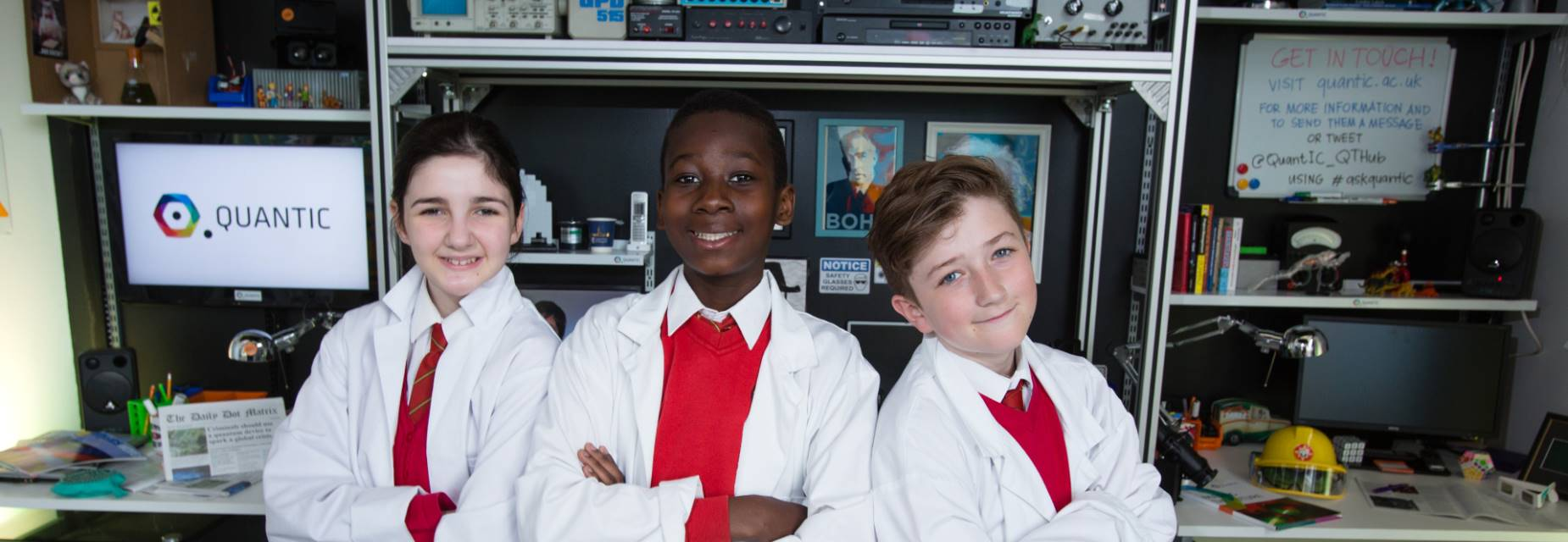 School pupils stand in front of an array of monitors and technical apparatus