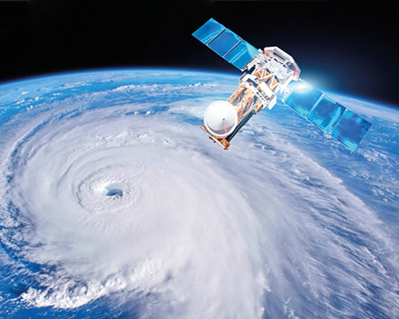 A satellite above Earth monitoring a storm
