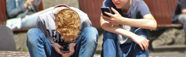 Two boys looking at phones