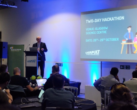 A speaker addresses a seated audience at the hackathon