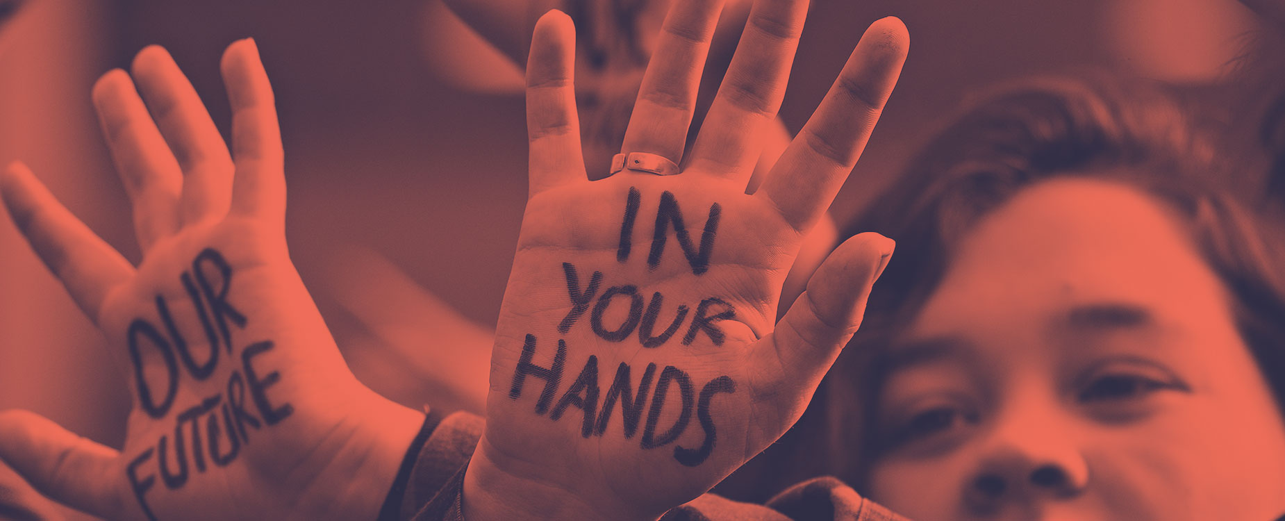 "A person with ""Our Future In Your Hands"" written on their hands"