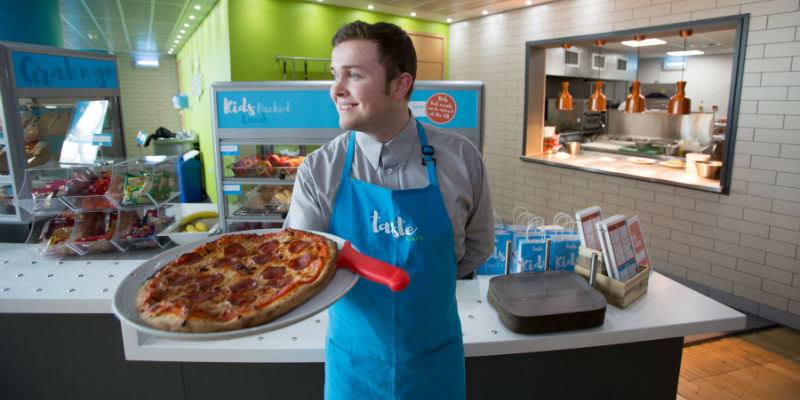 A waiter holds a plate of delicious pizza in front of the open kitchen area and sandwich counter at the Taste Cafe