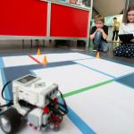 A boy and girl watch a robot they've programmed complete a set of tasks