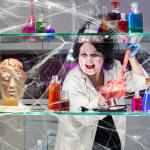 A scientist behind a web with potions, test tubes and model heads